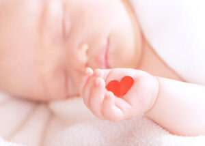 Photo of baby holding paper heart